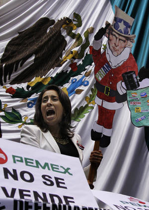 Photo - An opposition lawmaker in Mexico shouts while holding a protest banner as dozens of leftist lawmakers take over the lower house trying to block discussion of the energy reform bill Wednesday in Mexico City. AP Photo <strong>Marco Ugarte</strong>