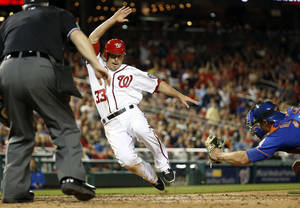 Photo - New York Mets catcher Anthony Recker, right, reaches to tag out Washington Nationals' Greg Dobbs,left, at home during the seventh inning of a baseball game at Nationals Park Friday, May 16, 2014, in Washington. The Nationals won 5-2. (AP Photo/Alex Brandon)