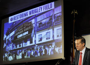 Photo - FILE - In this May 1, 2013, file photo, Chicago Cubs Chairman Tom Ricketts speaks in Chicago about proposed renovations at Wrigley Field. The owners of the Chicago Cubs say they're moving forward with plans to renovate and expand Wrigley Field, despite the threat of lawsuits by the owners of the adjacent rooftop venues overlooking the 100-year-old ballpark. Ricketts, whose family owns the north-side Chicago team, said Thursday, May 22, 2014 that the Cubs will submit a revised expansion plan to the Commission on Chicago Landmarks that includes the team's original proposal to add several outfield signs and additional bleacher seats. (AP Photo/Paul Beaty, File)