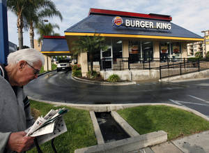 Photo - FILE - In this Thursday, April 25, 2013, file photo, a pedestrian walks past a Burger King restaurant near downtown Los Angeles. On Friday, April 25, 2014, Burger King reported a higher first-quarter profit as cost-cutting offset weak sales in the U.S. The Miami-based chain said global sales at established locations rose 2 percent, including a 0.1 percent increase in the U.S.(AP Photo/Nick Ut, File)