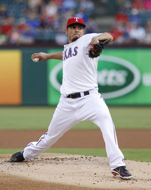 Photo - Texas Rangers starting pitcher Matt Garza throws to the New York Yankees during the first inning of a baseball game, Wednesday, July 24, 2013, in Arlington, Texas. (AP Photo/Jim Cowsert)