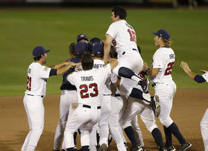 Photo - United States players celebrate after their 2-1 victory over Cuba an exhibition baseball game, Thursday, July 18, 2013, in Des Moines, Iowa. (AP Photo/Charlie Neibergall)