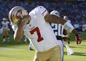 Photo - San Francisco 49ers quarterback Colin Kaepernick (7) celebrates after scoring a touchdown against the Tennessee Titans on a 20-yard run in the second quarter of an NFL football game on Sunday, Oct. 20, 2013, in Nashville, Tenn. (AP Photo/Mark Zaleski)