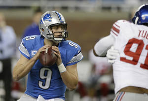 Photo - Detroit Lions quarterback Matthew Stafford (9) looks to pass during the first quarter of an NFL football game against the New York Giants, Sunday, Dec. 22, 2013, in Detroit. (AP Photo/Carlos Osorio)