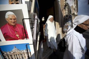 "photo - Two nuns walk past a photo of Pope Benedict XVI as they leave a souvenir shop just outside the Vatican, Tuesday, Feb. 26, 2013. Pope Benedict XVI will be known as ""emeritus pope"" in his retirement and will continue to wear a white cassock, the Vatican announced Tuesday, again fueling concerns about potential conflicts arising from having both a reigning and a retired pope. The pope's title and what he would wear have been a major source of speculation ever since Benedict stunned the world and announced he would resign on Thursday, the first pontiff to do so in 600 years. (AP Photo/Andrew Medichini)"