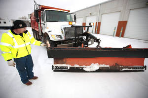 Photo - Snowplow driver Larry Fleming checks his plow before heeding out to clears streets in northwest Oklahoma City, Wednesday, December, 4, 2013. Photo by David McDaniel, The Oklahoman