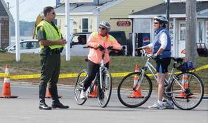 Photo - A Hampton, N.H. police officer directs bicyclists to a detour after the Neil R. Underwood Bridge was closed Saturday morning, Sept. 21, 2013 because of a fatal accident involving a car and five bicyclists participating in the Granite State Wheelers Seacoast Century ride. (AP Photo/Portsmouth Herald, Suzanne Laurent)