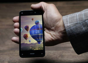 Photo - The new Amazon Fire Phone, displaying a dynamic perspective effect lock screen image, is posed for cameras after the official launch event, Wednesday, June 18, 2014, in Seattle. (AP Photo/Ted S. Warren)