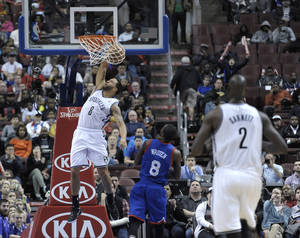 Photo - Brooklyn Nets' Deron Williams (8) dunks the ball over Philadelphia 76ers' Tony Wroten during the first half of an NBA basketball game on Saturday, April 5, 2014, in Philadelphia. (AP Photo/Michael Perez)