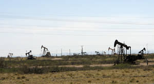 Photo - This April 9, 2014, photo shows oil rigs in the Loco Hills field in Eddy County, near Artesia, New Mexico, one of the most active regions of the Permian Basin. (AP Photo/Jeri Clausing)