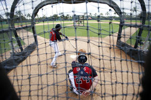 Photo - Atlanta Braves center fielder B.J. Upton (2) swings at a pitch with Evan Gattis (24) catching, during a spring training baseball workout, Monday, Feb. 24, 2014, in Kissimmee, Fla. (AP Photo/Alex Brandon)