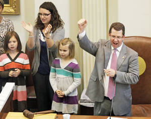 "photo - Oklahoma House Speaker Kris Steele, R-Shawnee, cheers Friday with, from left, his daughter, Mackenzie, 8, his wife, Kellie, and daughter, Madison, 6, as legislators and their families sing ""Oklahoma"" in the House chamber at the end of the legislative session.  Photo by Nate Billings, The Oklahoman"