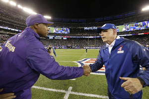 Photo - Minnesota Vikings head coach Leslie Frazier, left, shakes hands with New York Giants head coach Tom Coughlin after an NFL football game Monday, Oct. 21, 2013 in East Rutherford, N.J. The Giants won the game 23-7. (AP Photo/Julio Cortez)