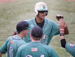 photo - STATE TOURNAMENT: Leedey's Drew Ward is congratulated by teammates after scoring a run during the Class B High School Baseball playoffs between Arnett and Leedey at the AT&T Bricktown Ballpark in Oklahoma City, OK, Saturday, Oct. 8, 2011. By Paul Hellstern, The Oklahoman ORG XMIT: KOD