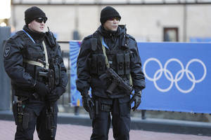 Photo - Russian security forces stand guard as the Olympic torch makes it's way through the streets of the Rosa Khutor ski resort in Krasnaya Polyana, Russia at the Sochi 2014 Winter Olympics, Wednesday, Feb. 5, 2014. (AP Photo/Gero Breloer)