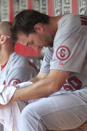 Photo - St. Louis Cardinals' Adam Wainwright rests in the dugout at the end of the fourth inning against the Cincinnati Reds during their baseball game in Cincinnati, Monday Sept. 2, 2013. (AP Photo/Tom Uhlman)