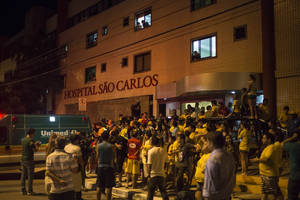 Photo - Soccer fans gather outside Sao Carlos Hospital where Brazil's soccer player Neymar was taken after being injured during the World Cup quarterfinal soccer match between Brazil and Colombia in Fortaleza, Brazil, Friday, July 4, 2014. Brazil's team doctor says Neymar will miss the rest of the World Cup after breaking a vertebrae during the team's quarterfinal win over Colombia. (AP Photo/Renata Brito)