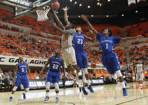 Photo - OSU COLLEGE BASKETBALL: Nate Maxey (23) and Hameed Ali (1) try to defend Fred Gulley (21) as he shoots a layup during the game between the Oklahoma State University Cowboys and the Texas A&M Corpus Christi Islanders at Gallagher-Iba Arena in Stillwater, Okla., Friday, Nov. 11, 2011. PHOTO BY MITCH ALCALA, FOR THE OKLAHOMAN. ORG XMIT: KOD