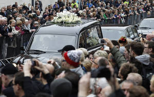 photo -   FILE - Crowds of people throng the route to watch the funeral cortege for Sir Jimmy Savile pass by in this file photo dated Wednesday Nov. 9, 2011, in Leeds, England. A year ago Savile was a cultural icon, but now on the first anniversary of the funeral, his reputation is laid low, his grave stone removed, and the people who revered him are trying to come to terms with his alleged sex crimes. (AP Photo/Jon Super, File)