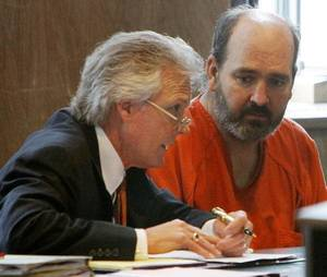photo - Stephen Paul Wolf, right,  listens to his attorney, Mack Martin, Friday in court.