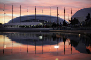 Photo - The sun sets as the Bolshoy Ice Dome is reflected in a pool of water underneath the Olympic cauldron at the 2014 Winter Olympics, Thursday, Feb. 13, 2014, in Sochi, Russia. (AP Photo/David Goldman)