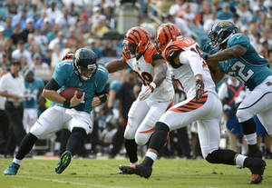 Photo -   FILE - This Sept. 30, 2012 filoe photo shows Jacksonville Jaguars quarterback Blaine Gabbert (11) getting sacked by Cincinnati Bengals outside linebacker Manny Lawson (99) and strong safety Taylor Mays (26) as running back Maurice Jones-Drew trails the play during the first half of an NFL football game in Jacksonville, Fla. The Bengals lead the NFL with 17 sacks heading into a game against Miami. (AP Photo/Phelan M. Ebenhack, File)