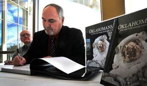Photo - A new book by former Oklahoma History Center archivist Bill Moore, right, pictured here signing his book in May, details Oklahoma's contributors to this country's space program, like former astronaut William Pogue, left. PHOTO BY DERRICK HO, THE OKLAHOMAN. <strong>Derrick Ho</strong>