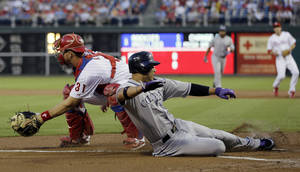 Photo -   Colorado Rockies' Carlos Gonzalez, right, scores past Philadelphia Phillies catcher Erik Kratz on a single by Wilin Rosario in the first inning of a baseball game, Friday, Sept. 7, 2012, in Philadelphia. (AP Photo/Matt Slocum)