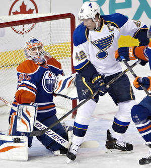 Photo - St. Louis Blues' David Backes (42) is stopped by Edmonton Oilers goalie Ilya Bryzgalov (80) during second period NHL hockey action in Edmonton, Canada, Tuesday, Jan. 7, 2014. (AP Photo/The Canadian Press, Jason Franson)