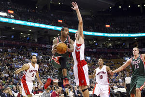 Photo -   Milwaukee Bucks' Monta Ellis, second from left, plays a pass beyond Toronto Raptors' Jonas Valanciunas during the first half of a preseason NBA basketball game, Monday, Oct. 22, 2012, in Toronto. (AP Photo/The Canadian Press, Chris Young)