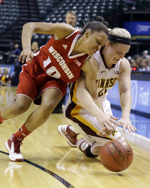 Photo - Wisconsin guard Dakota Whyte, left, and Minnesota guard Sari Noga go for a loose ball in the first half of an NCAA college basketball game in the opening round of the Big Ten Tournament in Indianapolis, Ind., Thursday, March 6, 2014. (AP Photo/Michael Conroy)
