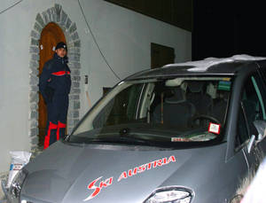 Photo - FILE - This is a Feb. 19, 2006 file photo of an Italian police officer as he stands outside a house where members of the Austrian Biathlon team were searched on the anti-doping police raid in San Sicario, Italy. You'd have to be a dope to try to get away with doping at the Sochi Olympics. That's the picture painted by international Olympic and anti-doping officials as they implement the toughest drug-testing program in Winter Games history.Using intelligence to target athletes and events considered most at risk, authorities are focusing their efforts on weeding out drug cheats through rigorous pre-games and pre-competition tests. (AP Photo/Tom Curley, FILE)