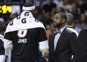 Photo - Miami Heat's Dwyane Wade, right, talks with LeBron James during the first half of an NBA basketball game against the Indiana Pacers, Friday, April 11, 2014, in Miami. Wade did not play due to a hamstring injury. (AP Photo/Lynne Sladky)