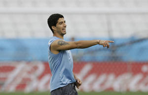 Photo - Uruguay national soccer team player Luis Suarez points whilst taking part in a squad training session for the 2014 soccer World Cup at Itaquerao Stadium in Sao Paulo, Brazil, Wednesday, June 18, 2014.  Uruguay play England in group D of the 2014 soccer World Cup at the stadium on Thursday.  (AP Photo/Matt Dunham)