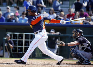 Photo - FILE - In this March 8, 2014, file photo, Houston Astros right fielder L.J. Hoes, left, bats in a spring exhibition baseball game against the New York Yankees in Kissimmee, Fla. Hoes' uncle, Kelly O'Bryan Hoes was 15 when he was killed by a drunk driver while crossing the street. L.J. Hoes never met Kelly, but on Tuesday, April 1, when Houston hosts the Yankees, L.J. will be on an opening day roster for the first time and he'll proudly wear the No. 28, his uncle's high school number. (AP Photo/Alex Brandon, File)