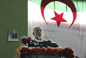 Photo -   Abdelaziz Belkhadem, head of Algeria's most powerful political party, the National Liberation Front, is back-dropped by a large national flag as he addresses supporters at a rally in Algiers, Sunday May 6, 2012, on the final day of campaigning ahead of Algeria's elections. Algerians are gearing up for legislative elections on upcoming Thursday and the government is urging people to vote to avoid the low turnouts of past contests. (AP Photo/Paul Schemm)
