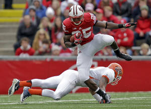 photo -   Wisconsin running back Melvin Gordon (25) runs over UTEP defensive back DeShawn Grayson during the first half of a NCAA college football game, Saturday, Sept. 22, 2012, in Madison, Wis. (AP Photo/Andy Manis)