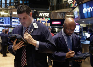 Photo - Robert McQuade, left, works with fellow traders on the floor of the New York Stock Exchange, Wednesday, Feb. 26, 2014. The stock market is little changed as investors pick over more earnings reports from retailers and other U.S. companies. (AP Photo/Richard Drew)