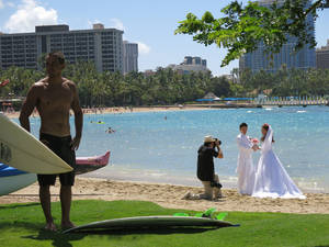 Photo - This May 21, 2014 photo shows surfer Kainoa Haas, 22, left, standing on grass fronting Duke Kahanamoku Beach  as a wedding couple is photographed in the Honolulu tourist neighborhood of Waikiki. The destination topped this year's annual ranking of the best public beaches in the United States as chosen by Stephen Leatherman, better known as Dr. Beach. (AP Photo/Sam Eifling)