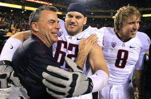 Photo - Arizona head coach Tim Kish, left, celebrates a win over Arizona State with players Chris Putton (62) and Nick Foles (8) after an NCAA college football game, Saturday, Nov. 19, 2011, in Tempe, Ariz.  Arizona defeated Arizona State 31-27. (AP Photo/Ross D. Franklin)