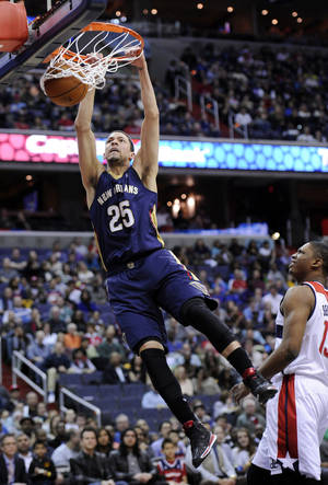 Photo - New Orleans Pelicans guard Austin Rivers (25) dunks against Washington Wizards center Kevin Seraphin, right, of France, during the first half of an NBA basketball game, Saturday, Feb. 22, 2014, in Washington. (AP Photo/Nick Wass)