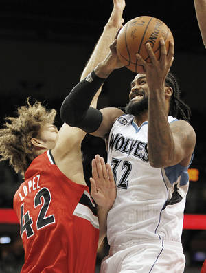 Photo - Minnesota Timberwolves center Ronny Turiaf (32) grabs a rebound from Portland Trail Blazers center Robin Lopez in the first quarter of their NBA basketball game on Saturday, Feb. 8, 2014 in Minneapolis.(AP Photo/Andy Clayton-King)