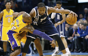 Photo - Oklahoma City Thunder forward Kevin Durant (35) keeps the ball away from Los Angeles Lakers Kobe Bryant (24) in the second quarter of an NBA basketball game in Oklahoma City, Friday, Dec. 13, 2013. (AP Photo/Sue Ogrocki)