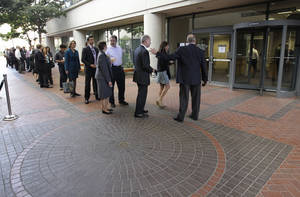 Photo -   People wait in line to get inside for the Apple and Samsung trial during a lunch break at a federal courthouse in San Jose, Calif., Tuesday, Aug. 21, 2012. After three weeks of listening to technology experts, patent professionals and company executives debate the complicated legal claims of Apple Corp. and Samsung Electronics Co., a jury of nine men and women are set to decide one of the biggest technology disputes in history. (AP Photo/Paul Sakuma)