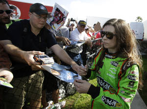 photo - Driver Danica Patrick, right, signs autographs for fans after the morning session of NASCAR auto race testing at Daytona International Speedway, Thursday, Jan. 10, 2013, in Daytona Beach, Fla. (AP Photo/John Raoux)