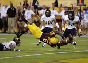 photo -   Arizona State running back Cameron Marshall, center, dives into the end zone for a touchdown against the Northern Arizona defense during the first half of their NCAA college football game on Thursday, Aug. 30, 2012, in Tempe, Ariz. (AP Photo/Rick Scuteri)