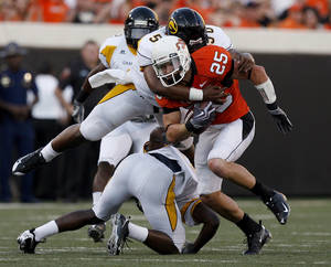 Photo - OSU's Josh Cooper (25) is tackled by Grambling's Cliff Exama (50) during the college football game between the Oklahoma State University Cowboys (OSU) and the Grambling State University Tigers (GSU) at Boone Pickens Stadium in Stillwater, Okla., Saturday, September 26, 2009. Photo by Sarah Phipps, The Oklahoman ORG XMIT: KOD