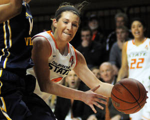 Photo - Cowgirl guard Liz Donohoe dribbles around a defender to the baseline during the Cowgirl's conference opener against West Virginia. West Virginia went on to defeat Oklahoma State 71-67 at Gallagher Iba Arena in Stillwater on Jan. 4, 2014.   Photo by KT King/For the Oklahoman