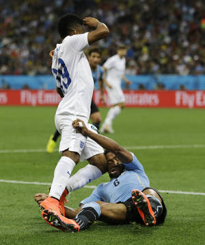 Photo - England's Raheem Sterling runs into Uruguay's Alvaro Pereira with his knee during the group D World Cup soccer match between Uruguay and England at the Itaquerao Stadium in Sao Paulo, Brazil, Thursday, June 19, 2014. Pereira was knocked out by the blow.  (AP Photo/Kirsty Wigglesworth)