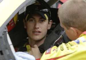 Photo - Joey Logano (22) listens to his crew  before the NASCAR Sprint Cup series auto race at Chicagoland Speedway in Joliet, Ill., Sunday, Sept. 15, 2013. (AP Photo/Nam Y. Huh)